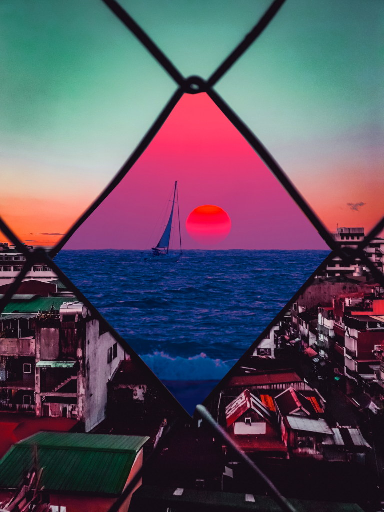 Image of a chain linked fence, the foreground slum-like while the center of the chain shows a beautiful sail boat coasting in the sunset